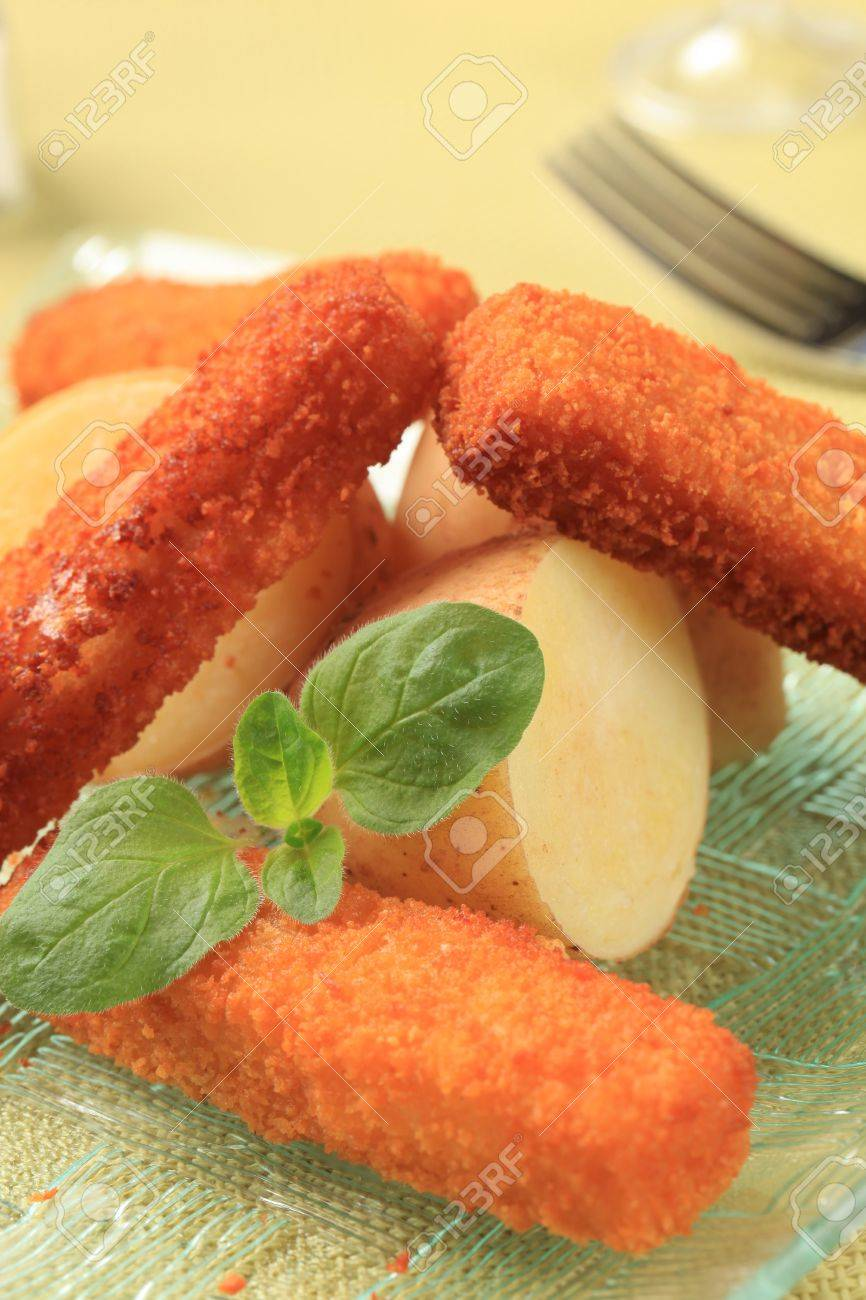 Fried fish fingers and new potatoes - detail Stock Photo - 9612608