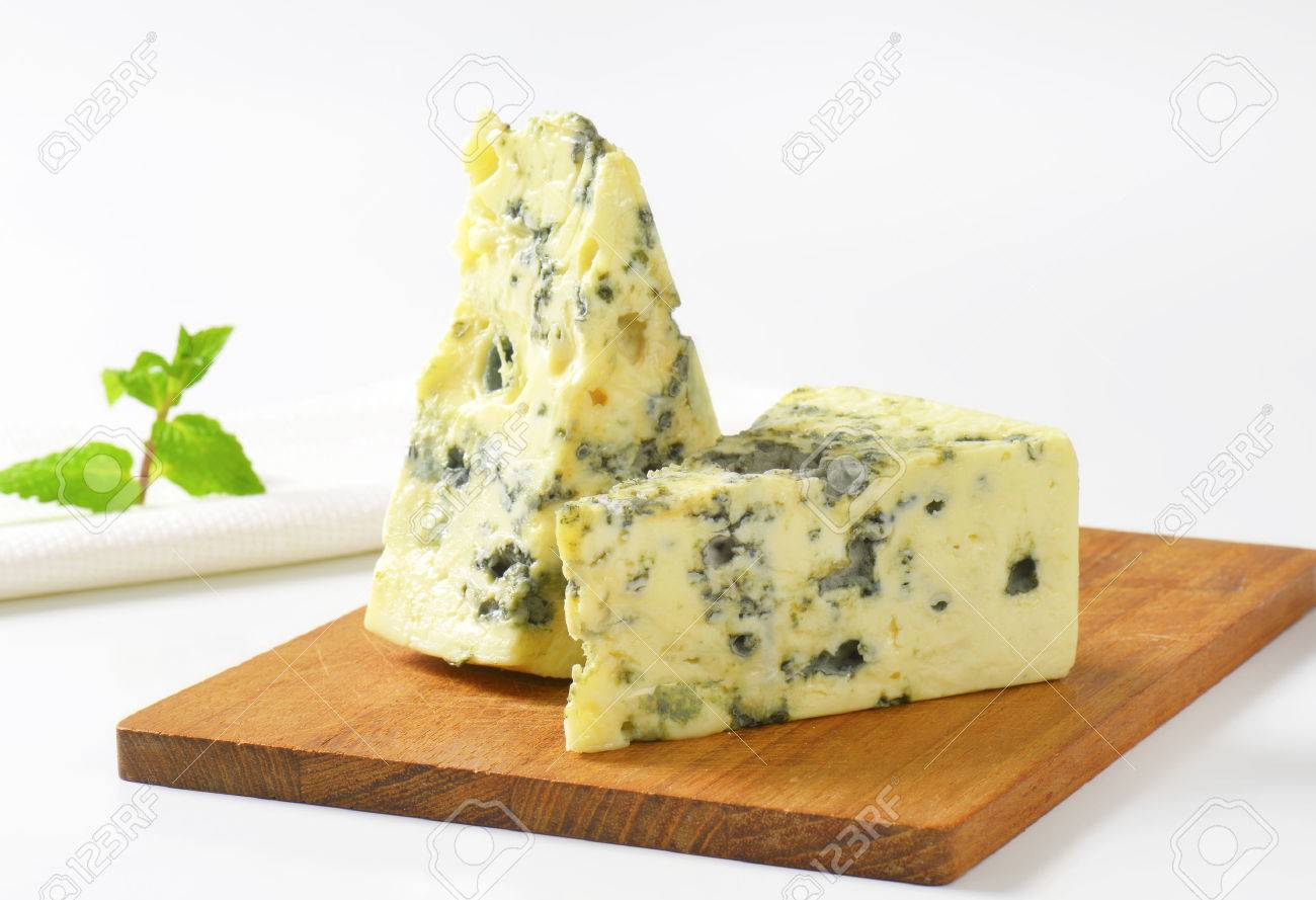 two wedges of french blue cheese on cutting board stock photo