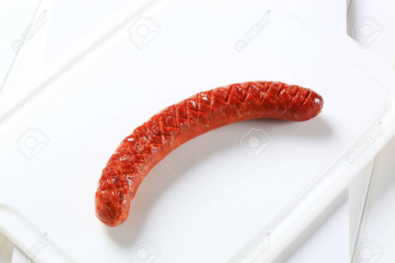 Grilled spicy sausage on white cutting board - 75677158