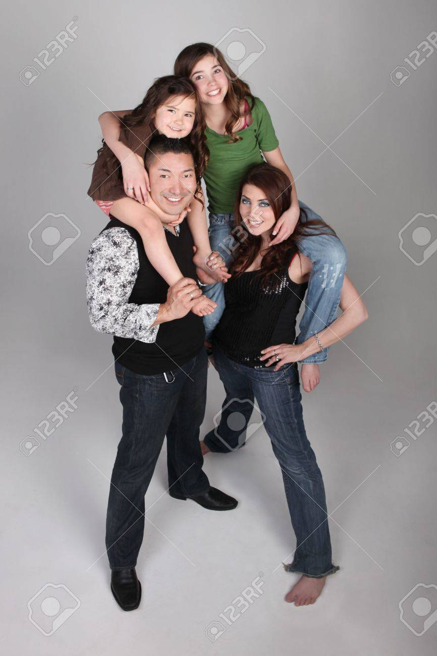 Fun and Unusual Family Portrait of Husband Wife and 3 Daughters on Grey Background Stock Photo - 4595941