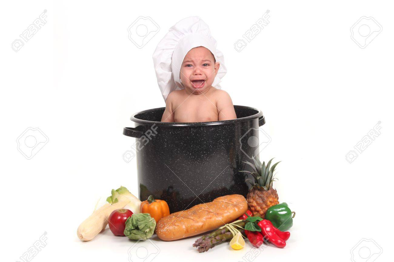 Screaming baby boy crying during a portrait shoot in a chef pot prop set stock photo