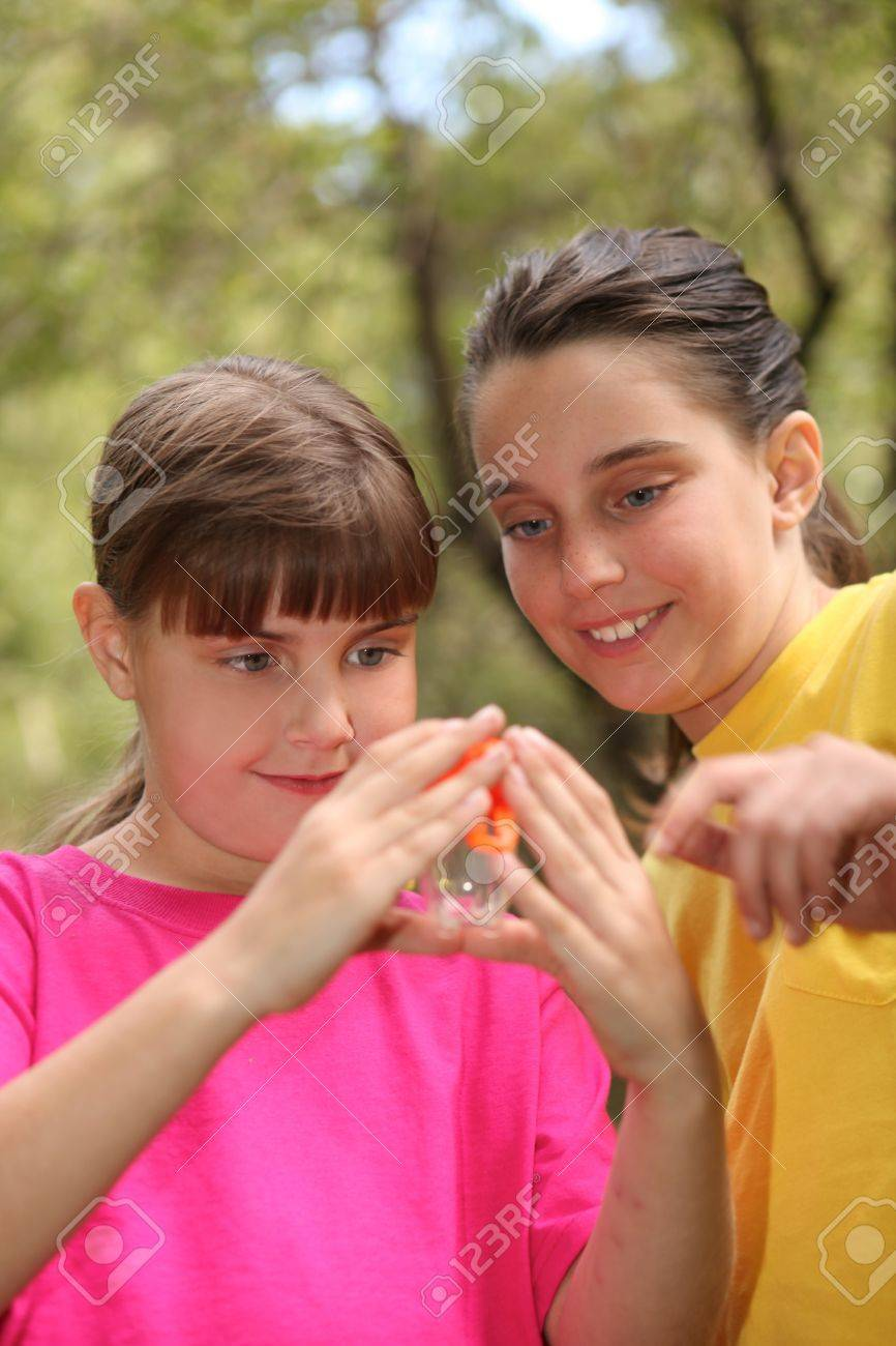 Sibling Girls Hunting for Insects While Camping Outdoors Stock Photo - 11227158