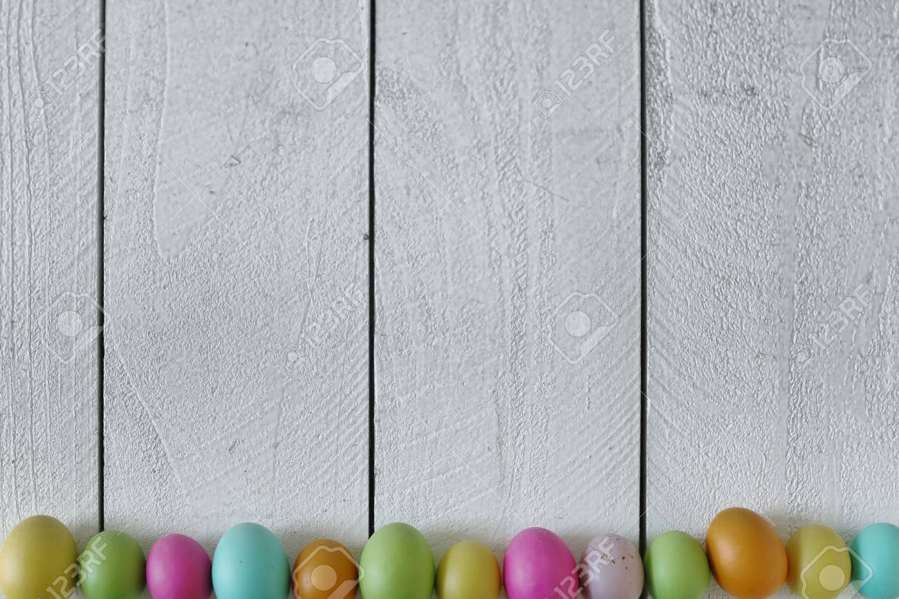 spring or easter themed background of old wood and colored eggs