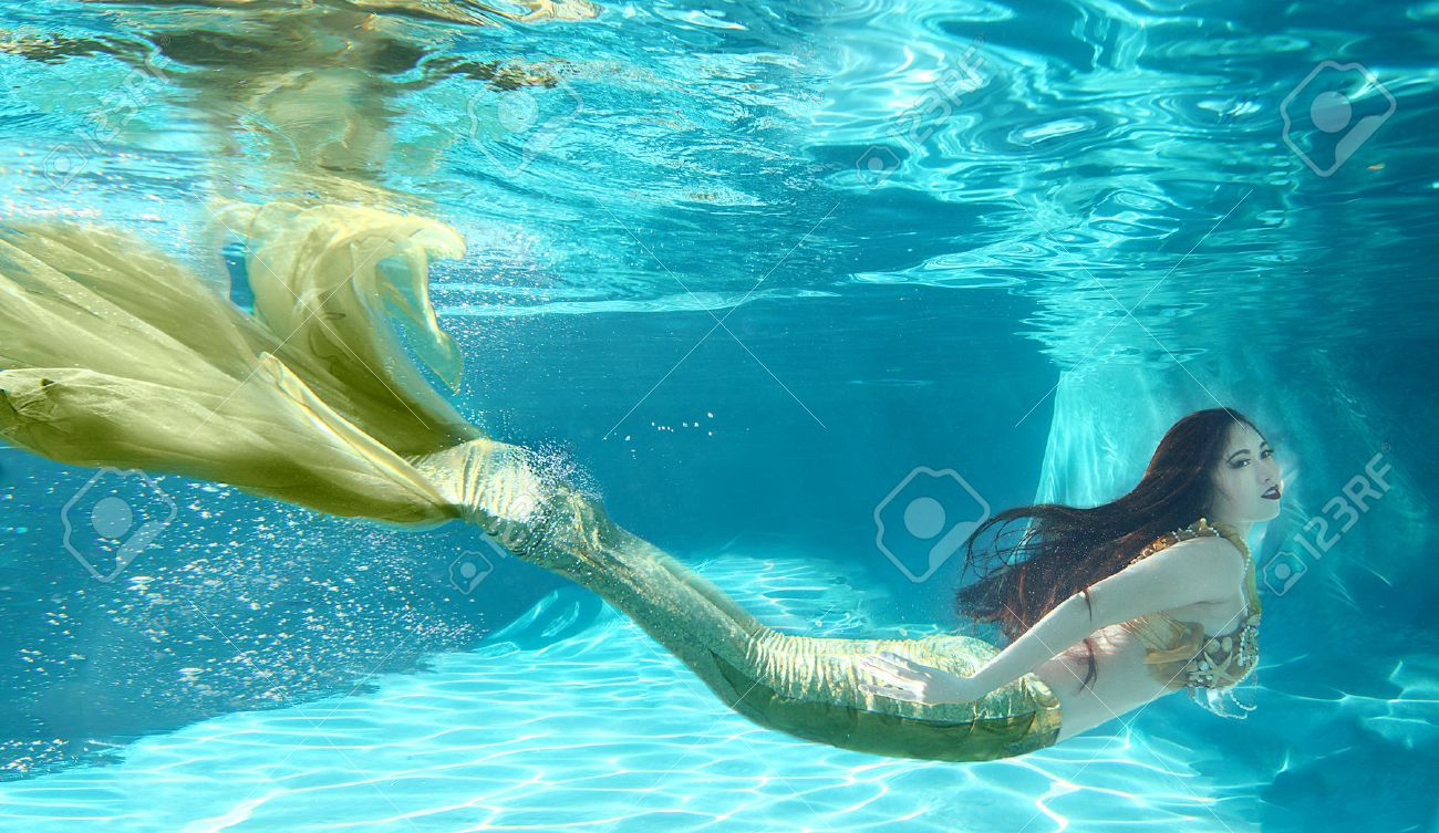 Woman Swimming Like A Mermaid Underwater Outdoors Stock Photo
