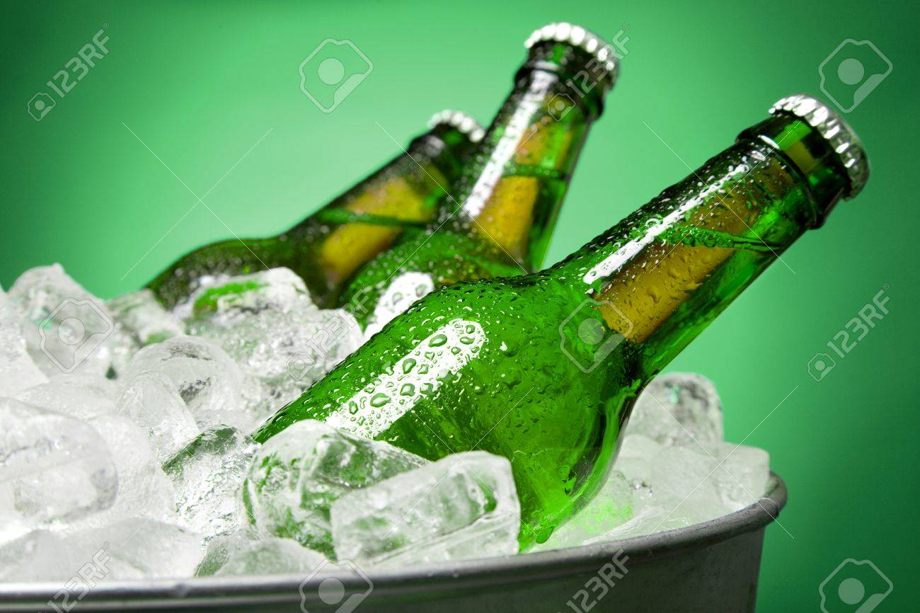 Three green bottles of beer chilling on ice in a tub against a green background Stock Photo - 9026364