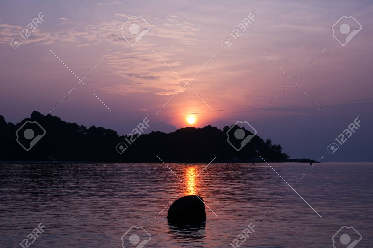 Golden sun setting behind island into the ocean with a purple colored background sky and a rock in the ocean. - 74741396