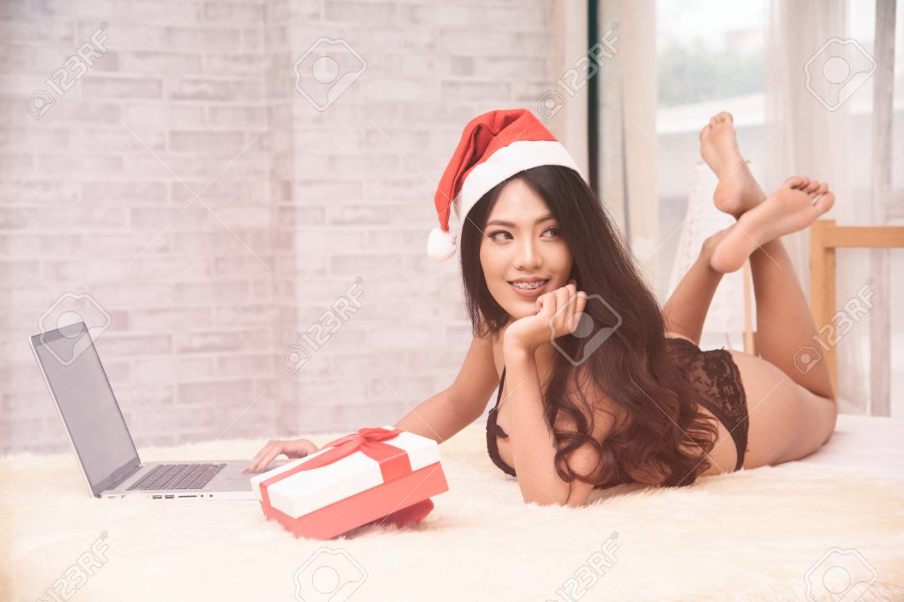 af6cac88f69f7 sexy christmas girl wearing bikini and santa hat with holding gift box red  ribbon lying on
