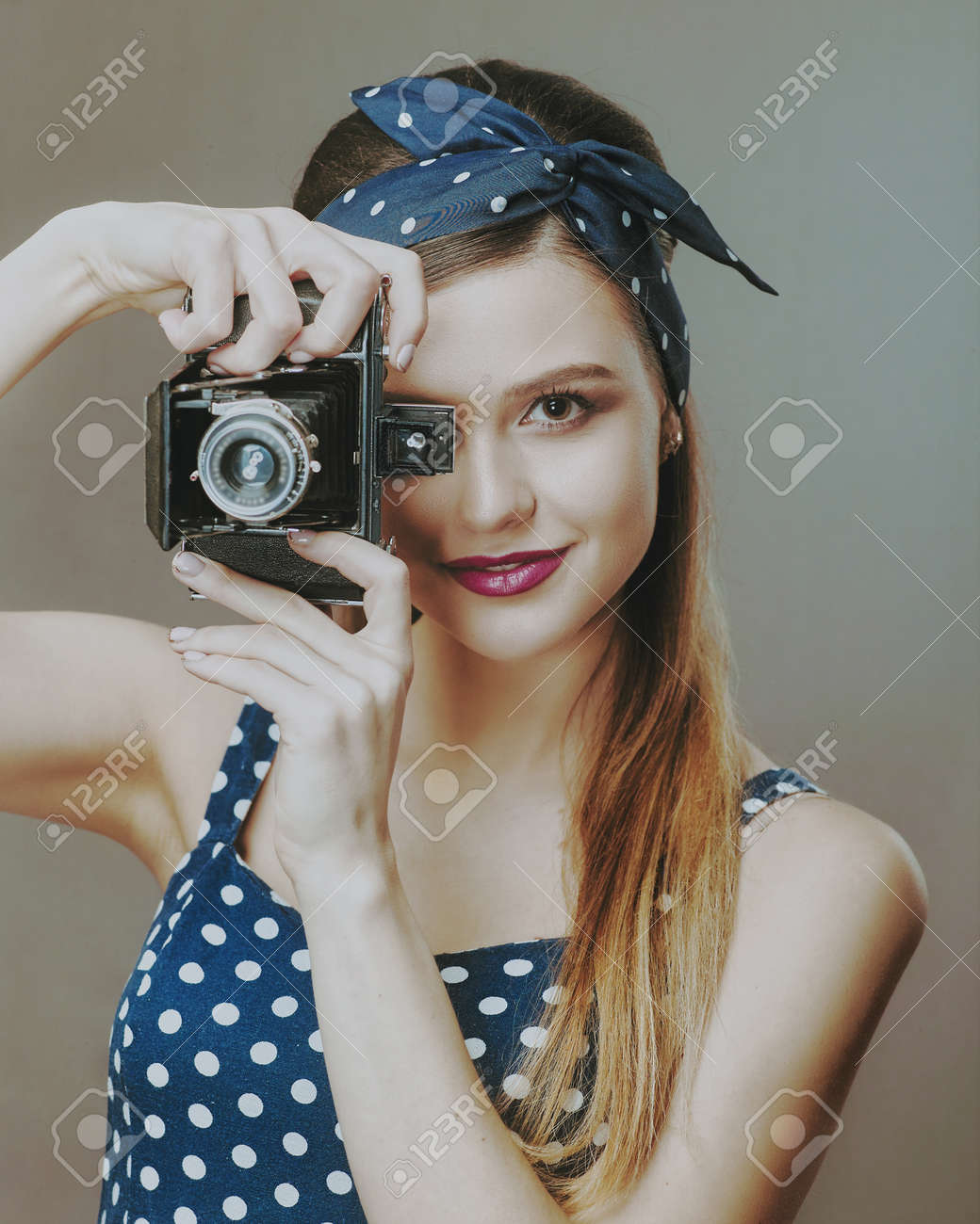 Photographer. Female Pinup Portrait. Young adult woman posing with vintage photo camera - 159316742