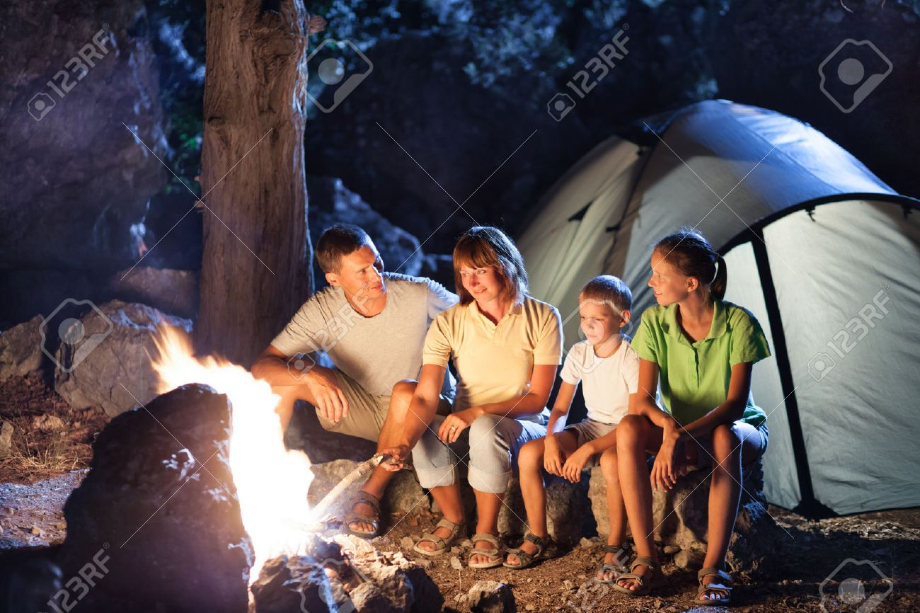 Family Camping With Campfire At Night Stock Photo