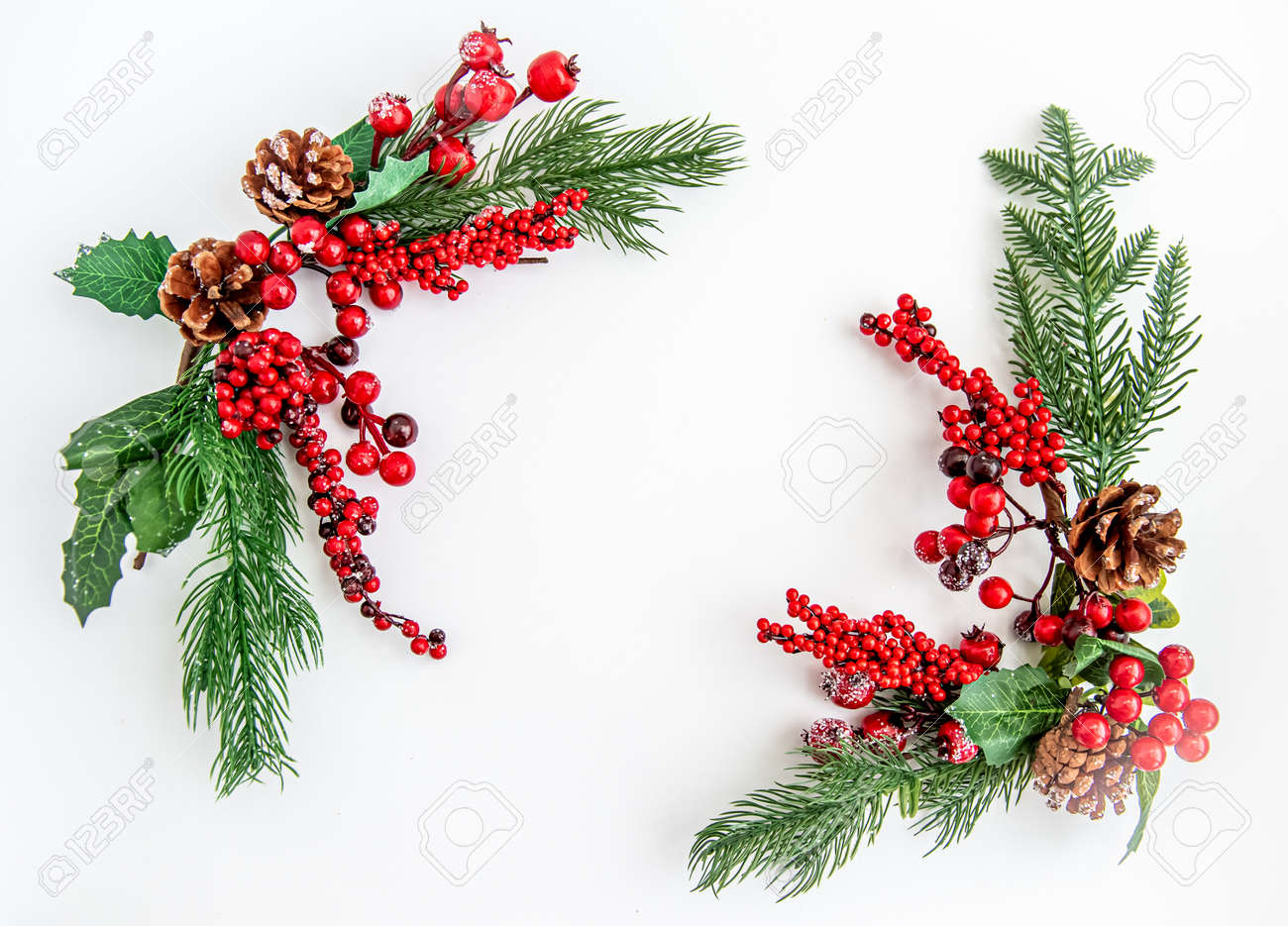 Green fir branches with red berries and Christmas decorations on a white background. Merry Christmas or Happy New Year concept. Flat lay, top view, copy space - 159765461