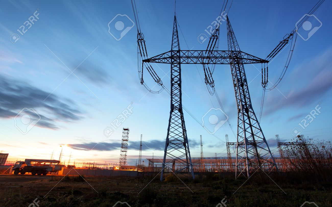 electricity transmission pylon silhouetted against blue sky at dusk - 53132216