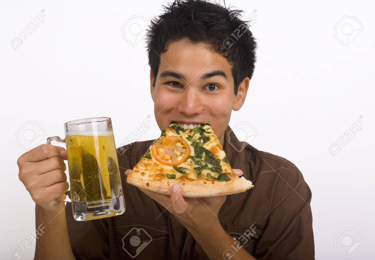 A young Asian American man enjoys a glass of beer and a slice of pizza Stock Photo - 4357398