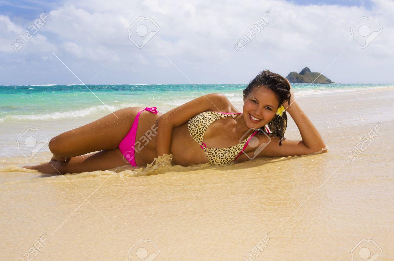a beautiful young Polynesian girl in a pink bikini lying on a Hawaii beach Stock Photo - 4540287
