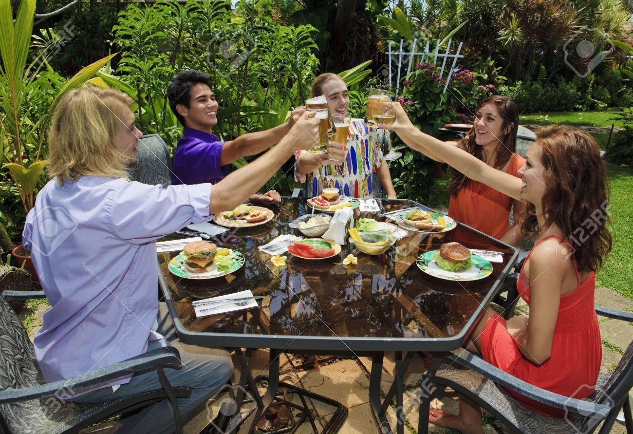 friends at a backyard bar b que in hawaii raising their glasses