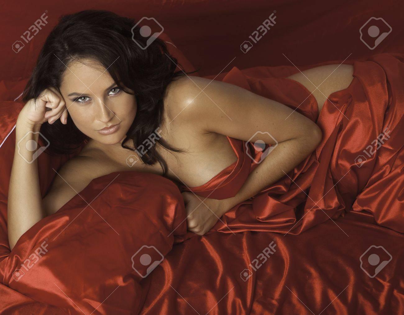 beautiful woman on red satin sheets Stock Photo - 20570575