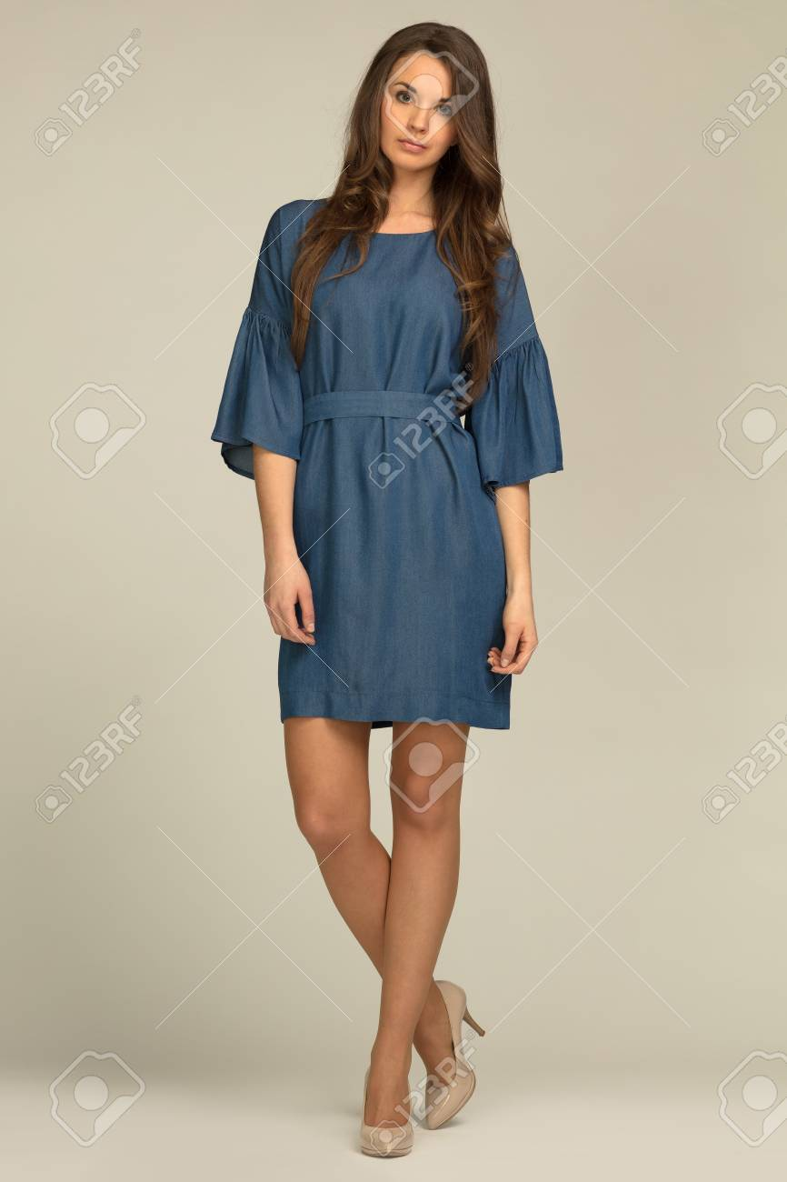 Model With Charming Hairstyle Wearing Jeans Dress Stock Photo