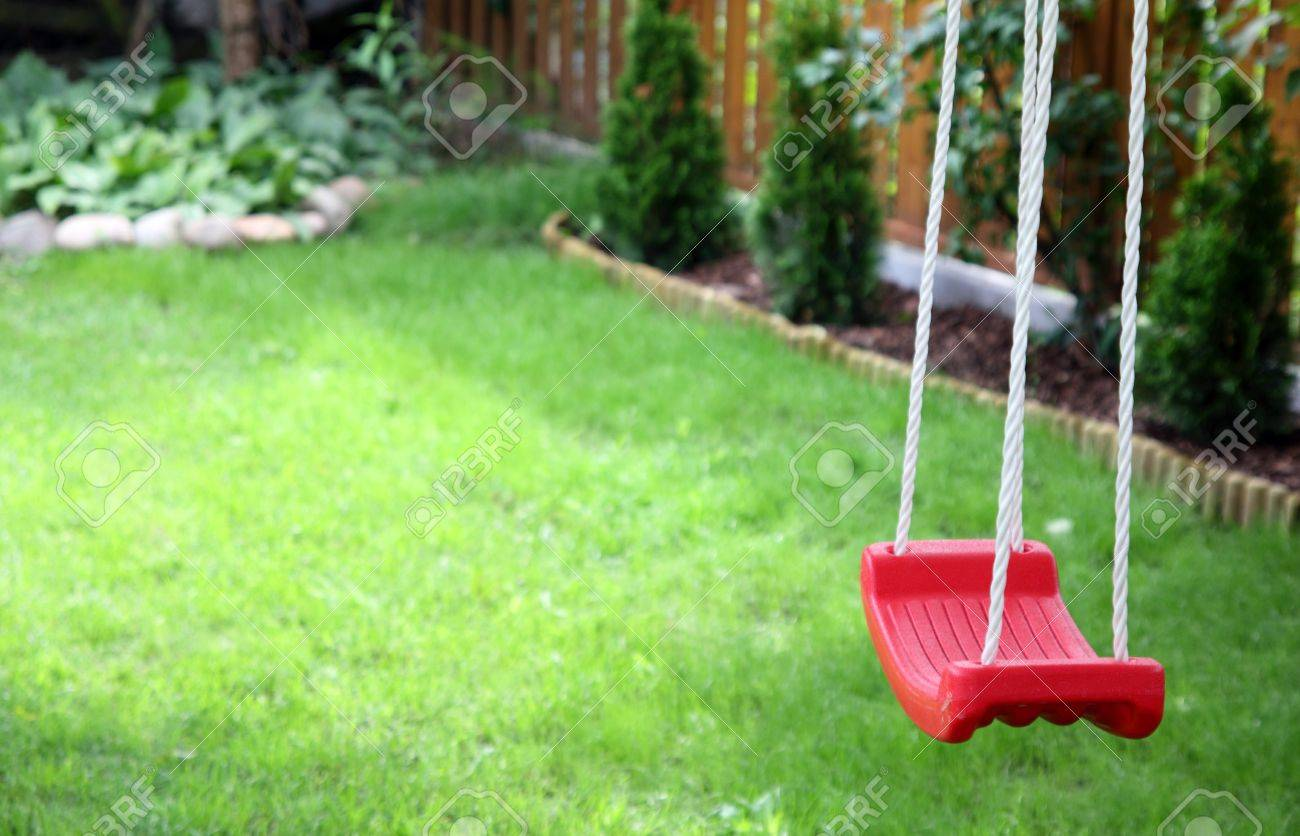 An empty child's swing on green grass background Stock Photo - 7905413