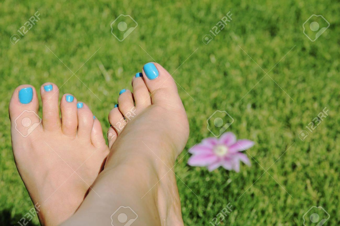 Mujer De Pie Con Las Uñas Azules Sobre Fondo De Hierba Con Flores ...