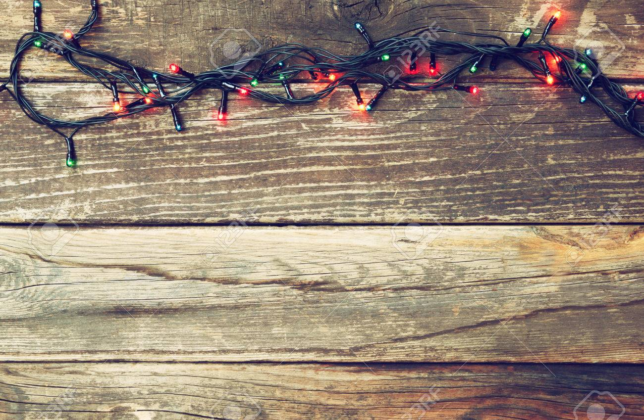 Colorful Christmas Lights On Wooden Rustic Background Filtered Image Stock Photo