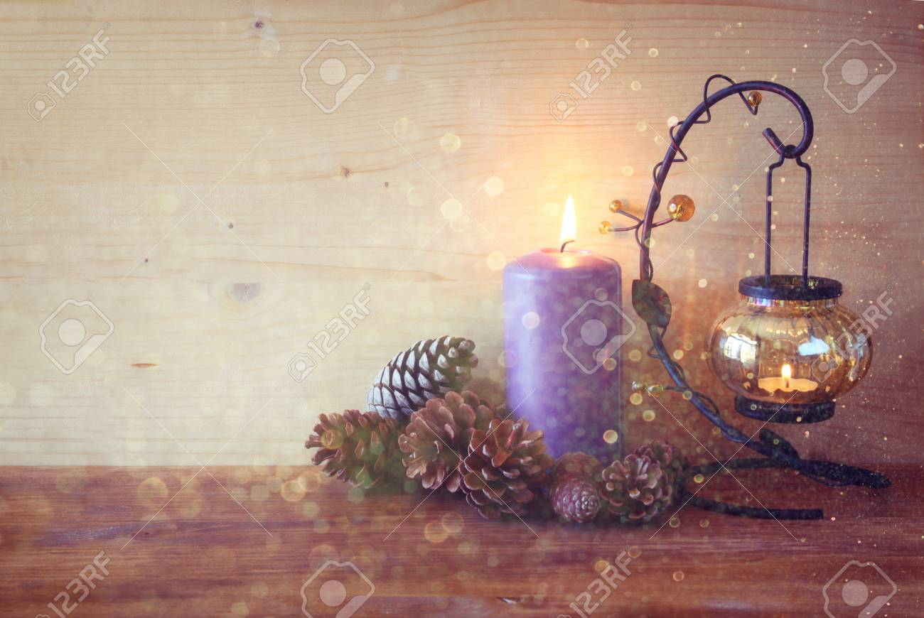 vintage Lantern with burning candles, pine cones on wooden table