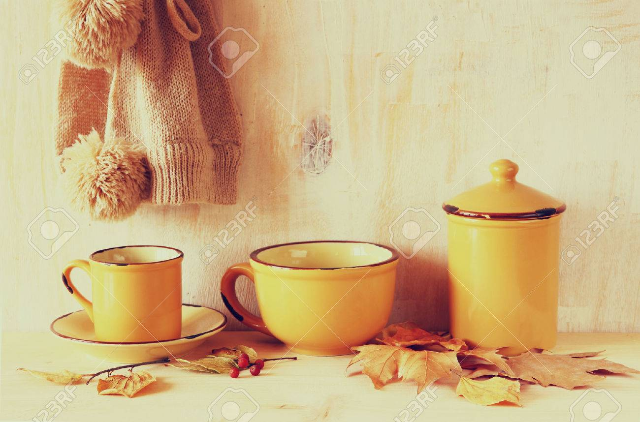 b7c9b0176ce set of vintage coffee mugs and jar over rustic textured wooden table and autumn  leaves.