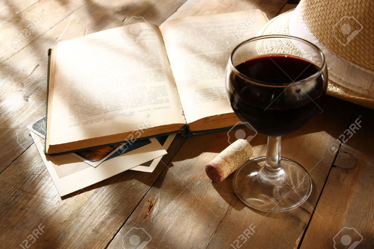 Red Wine Glass And Old Book On Wooden Table At Sunset Burst Stock