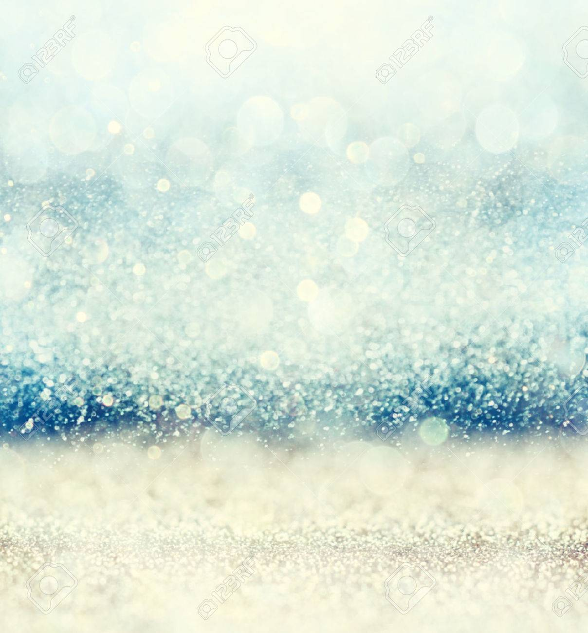 glitter vintage lights background with light burst gold blue and white defocused stock
