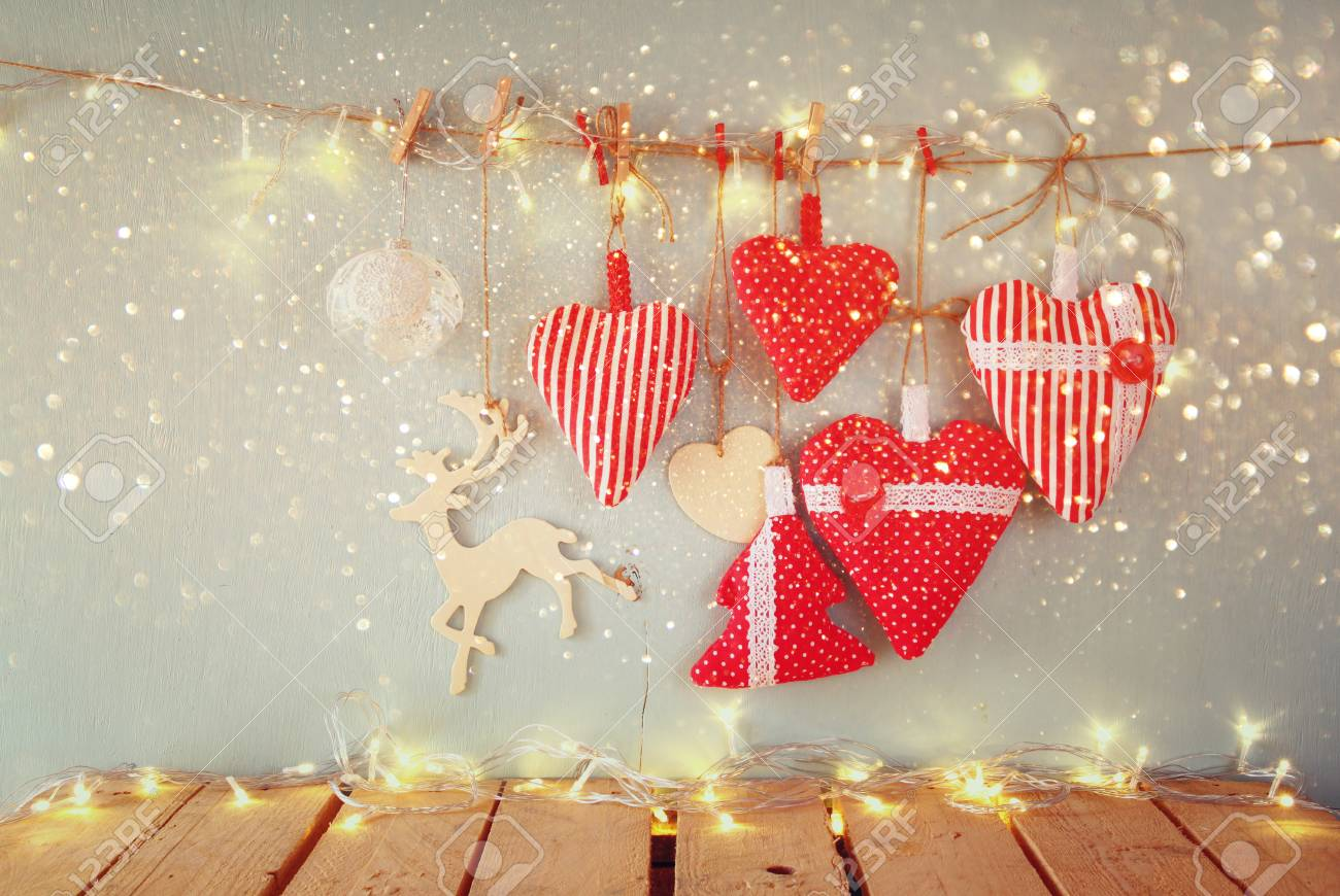 Retro Weihnachtsbilder.Christmas Image Of Fabric Red Hearts And Garland Lights Hanging On Rope In Front Of Blue Wooden Background Retro Filtered