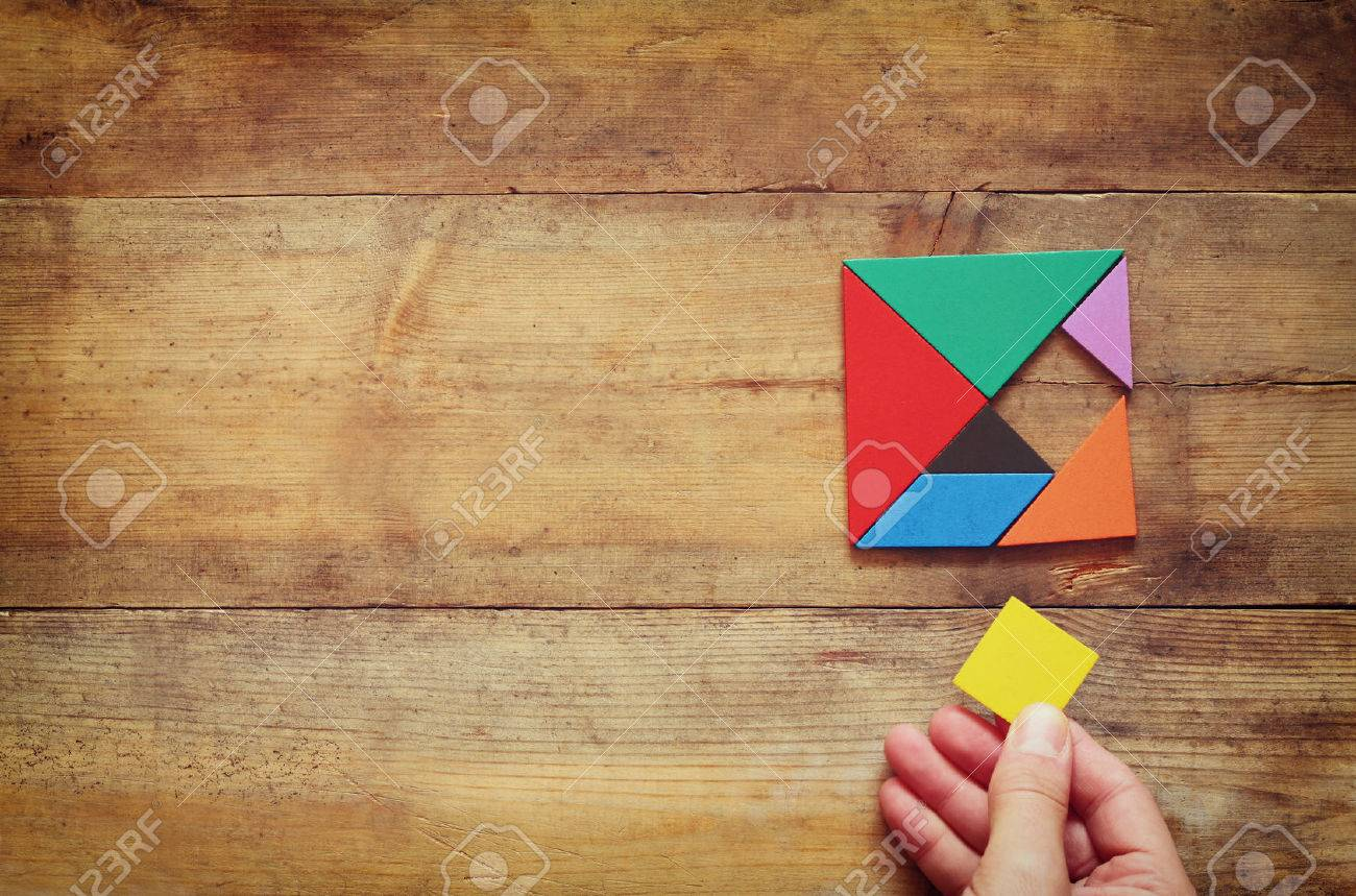man's hand holding a missing piece in a square tangram puzzle, over wooden table. - 50536862