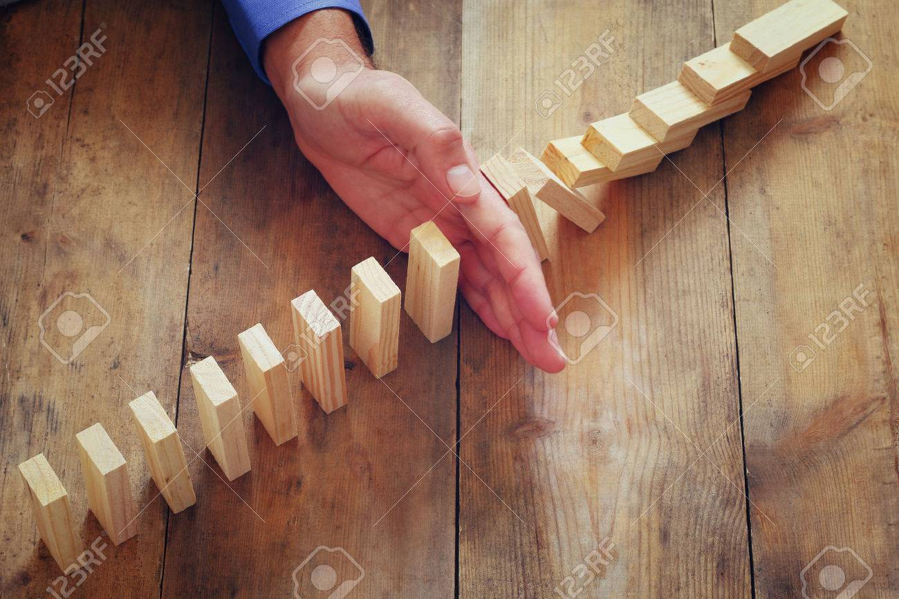 a male hand stoping the domino effect. retro style image executive and risk control concept Stock Photo - 50537271