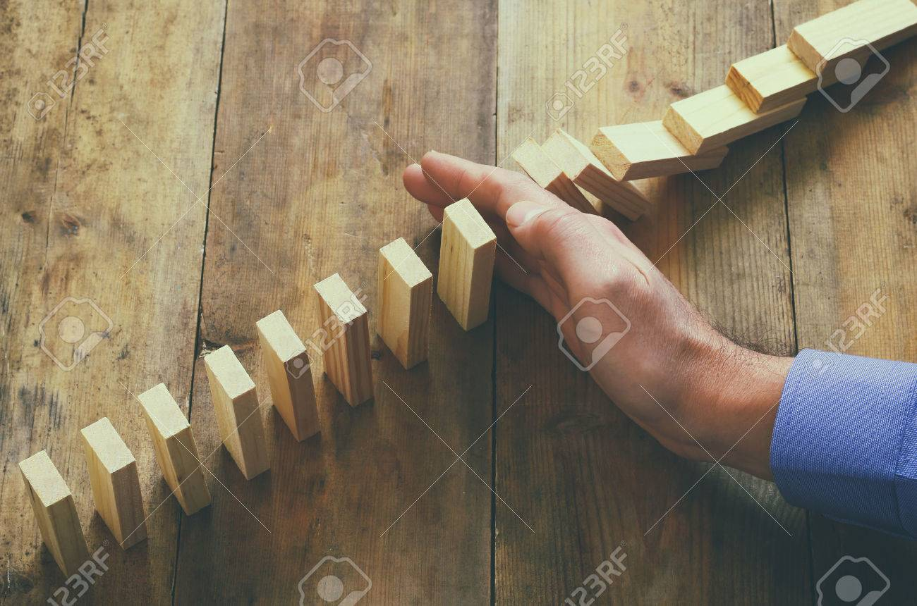 a male hand stoping the domino effect. retro style image executive and risk control concept - 51155351