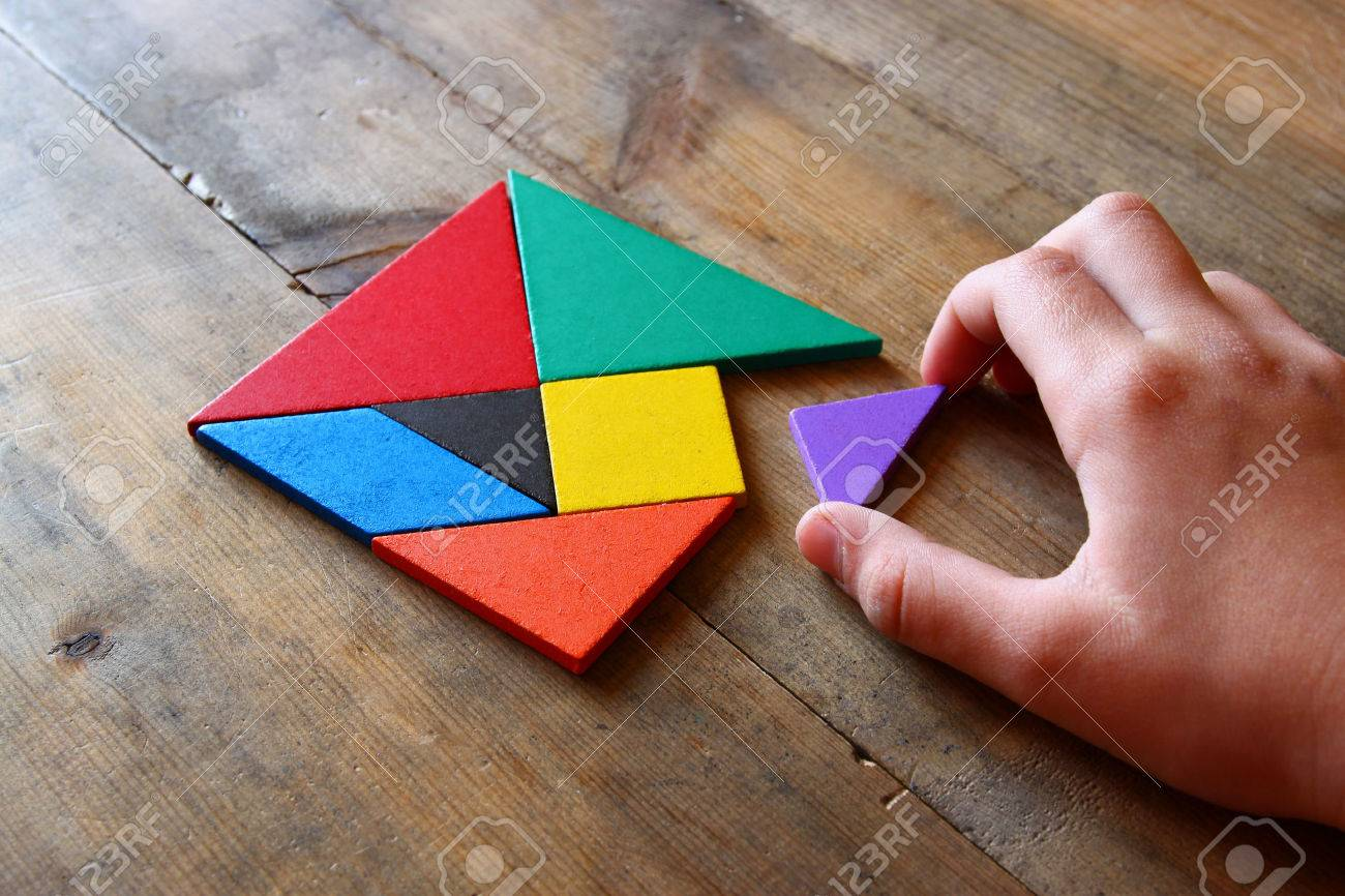 man's hand holding a missing piece in a square tangram puzzle, over wooden table. - 51155985
