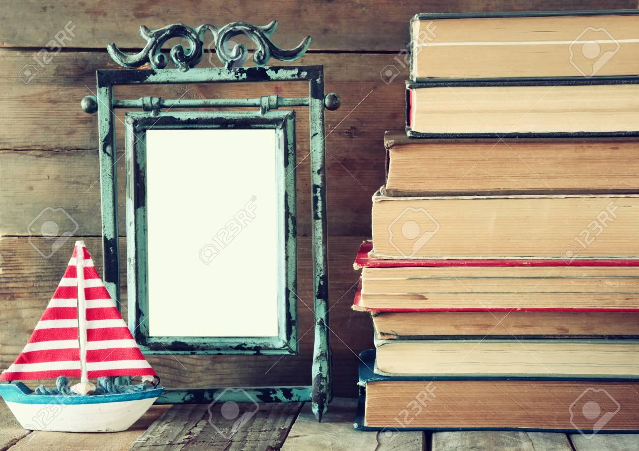 Pile De Livres Anciens à Côté De Décoration Voilier Et Cadre Blanc