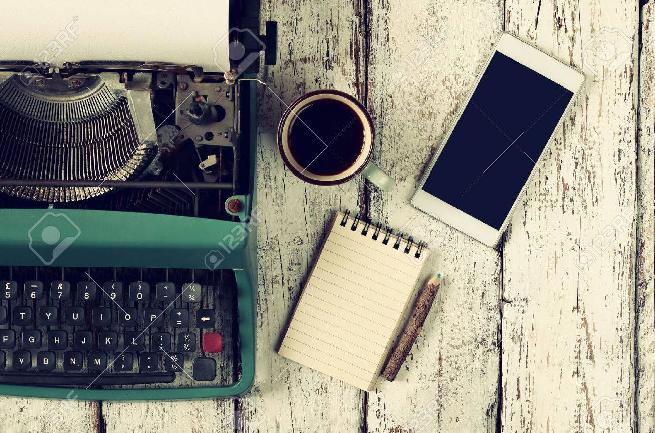 retro filtered image of vintage typewriter, blank notebook, cup of coffee and smartphone on wooden table - 51657494