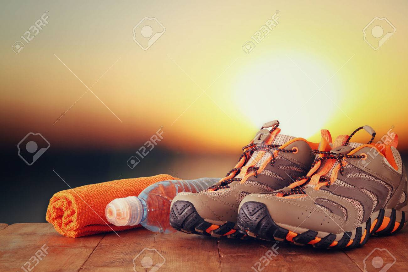 fitness concept with sport footwear, towel and water bottle over wooden table in front of sunset landscape. - 53375267