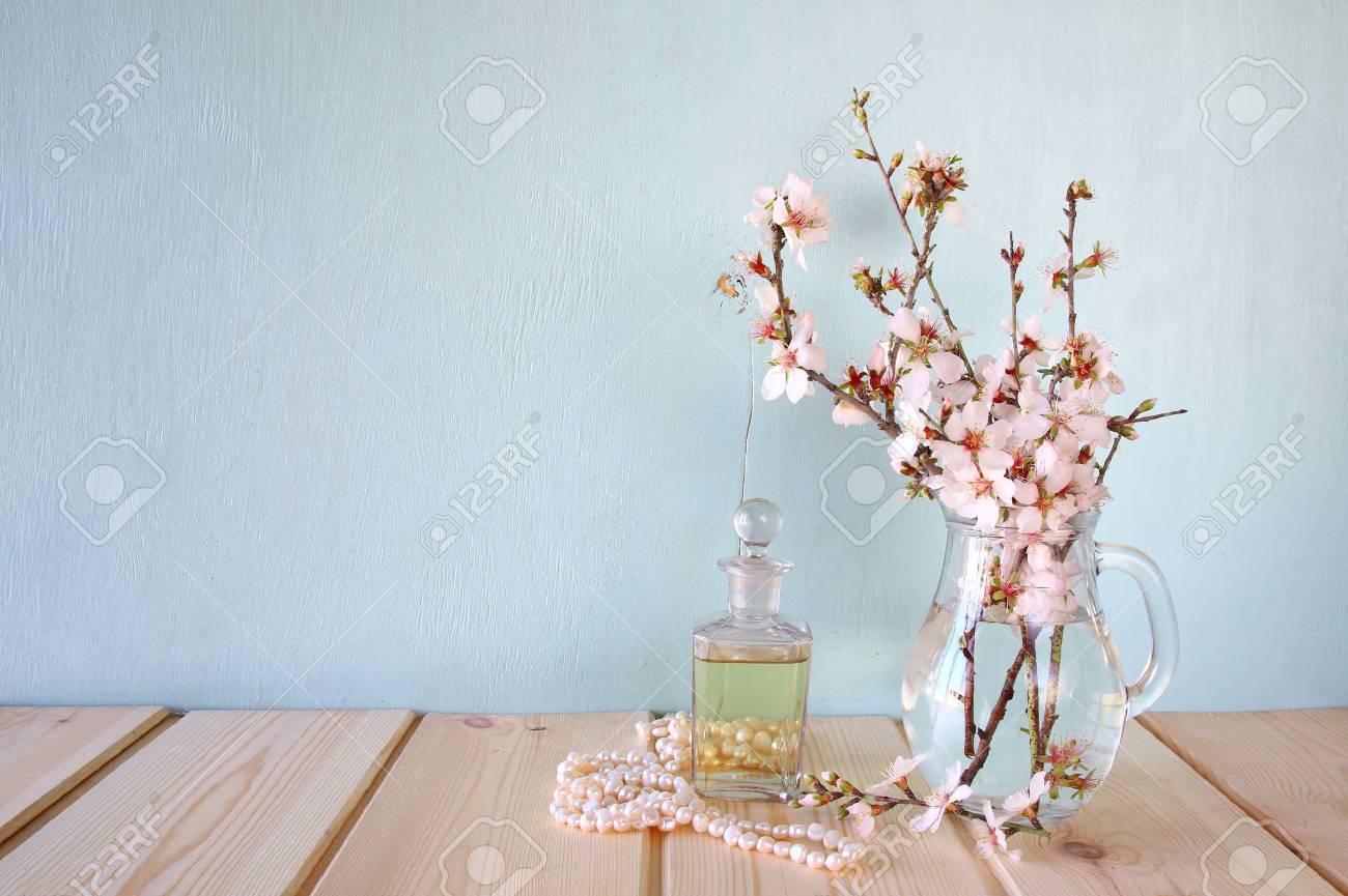 Fresh Vintage Perfume Bottle Next To White Spring Flowers On Stock