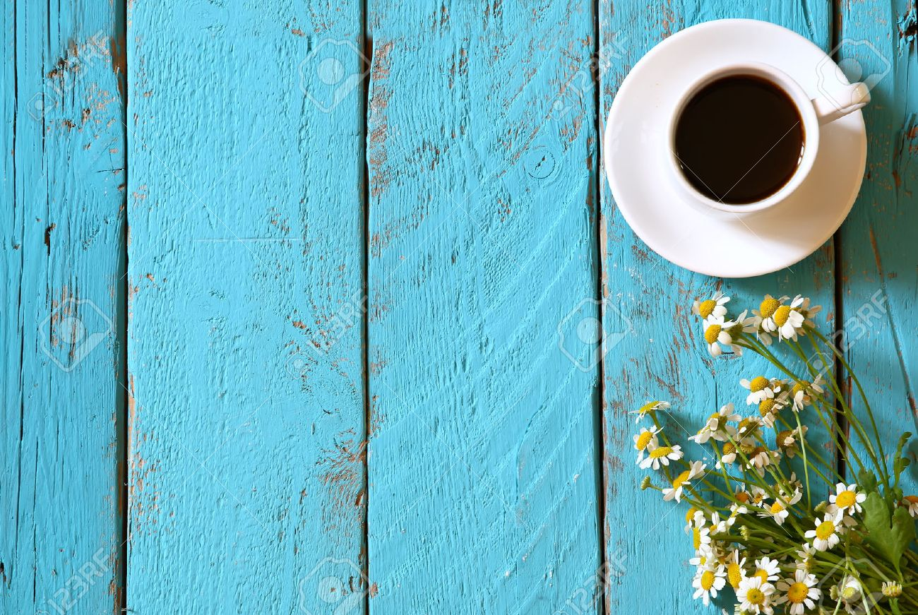 top view image of daisy flowers next to cup of coffee on blue wooden table Stock Photo - 53609724