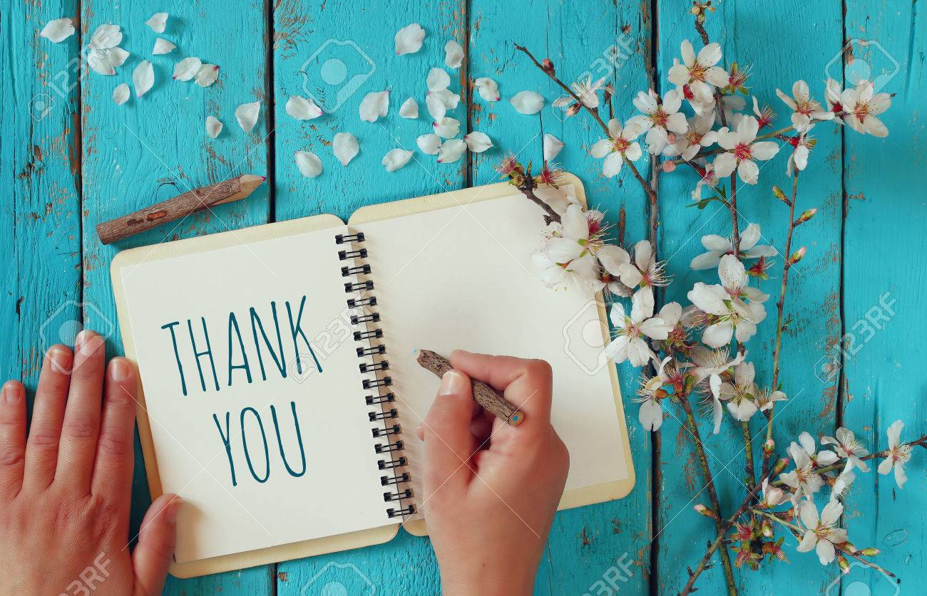 woman hand writing a note with the text thank you on a notebook, over wooden table and cherry blossom flowers Stock Photo - 53663620
