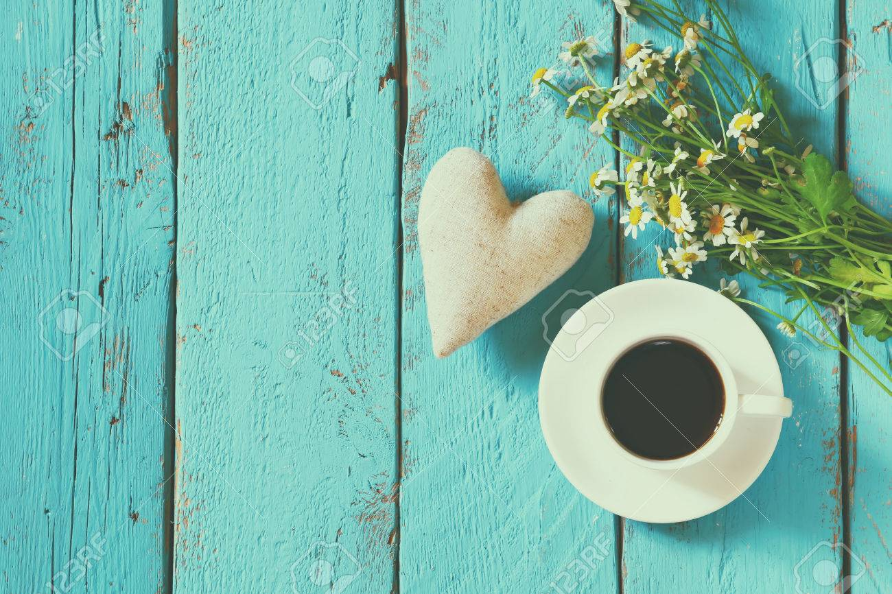top view image of daisy flowers and fabric heart next to cup of coffee on blue wooden table. vintage filtered and toned Stock Photo - 53665466