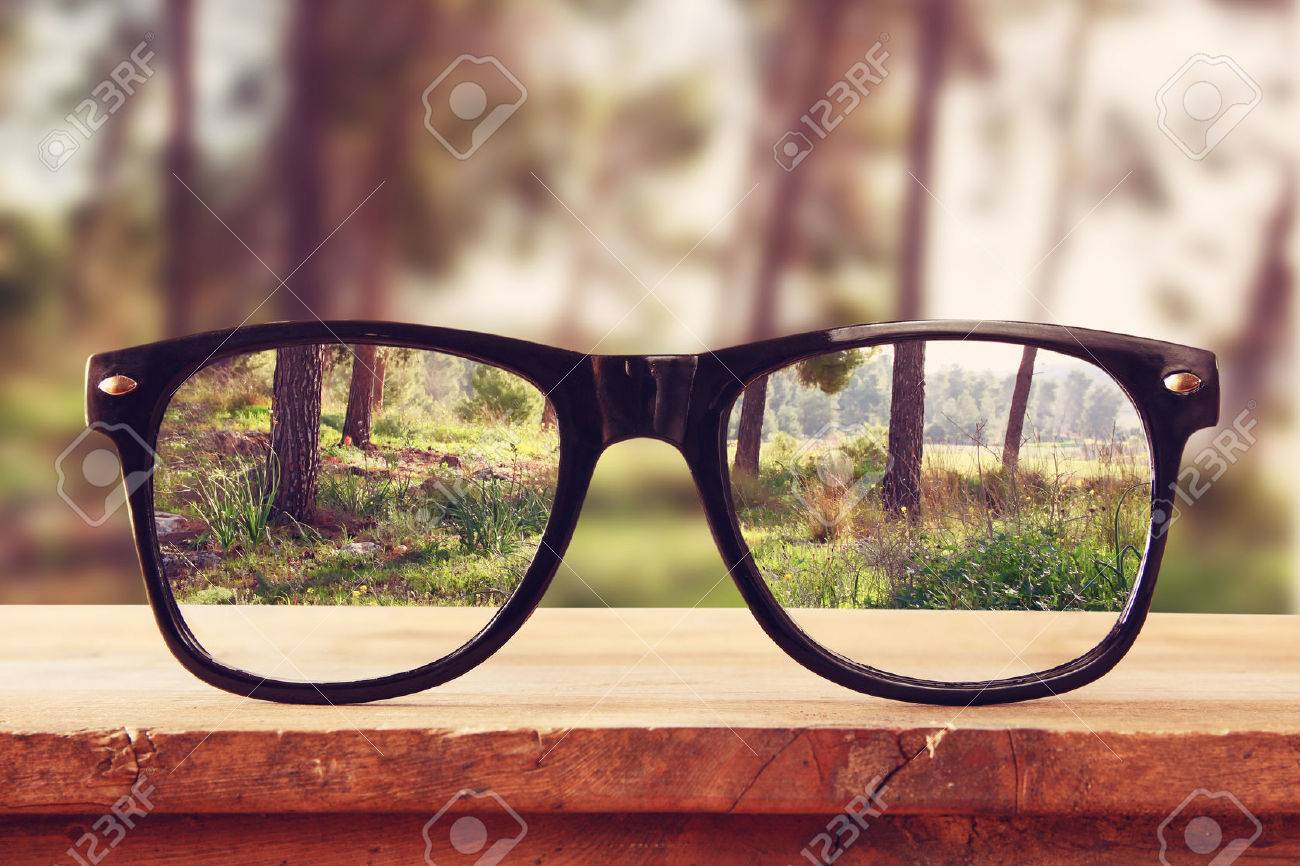 hipster glasses on a wooden rustic table in front of the forest. vintage filtered Stock Photo - 54512048