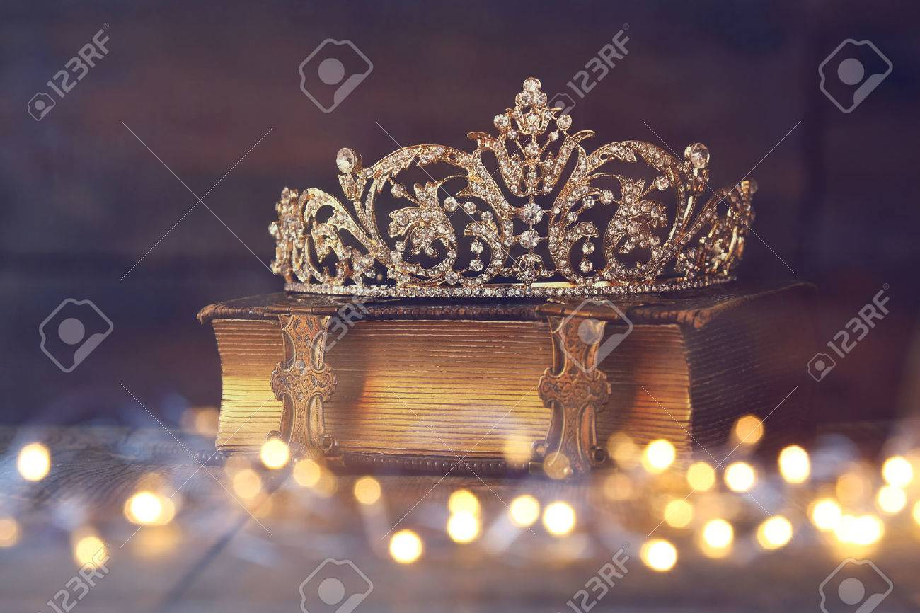 low key image of decorative crown on old book. vintage filtered with flitter overlay. selective focus. Stock Photo - 55592408