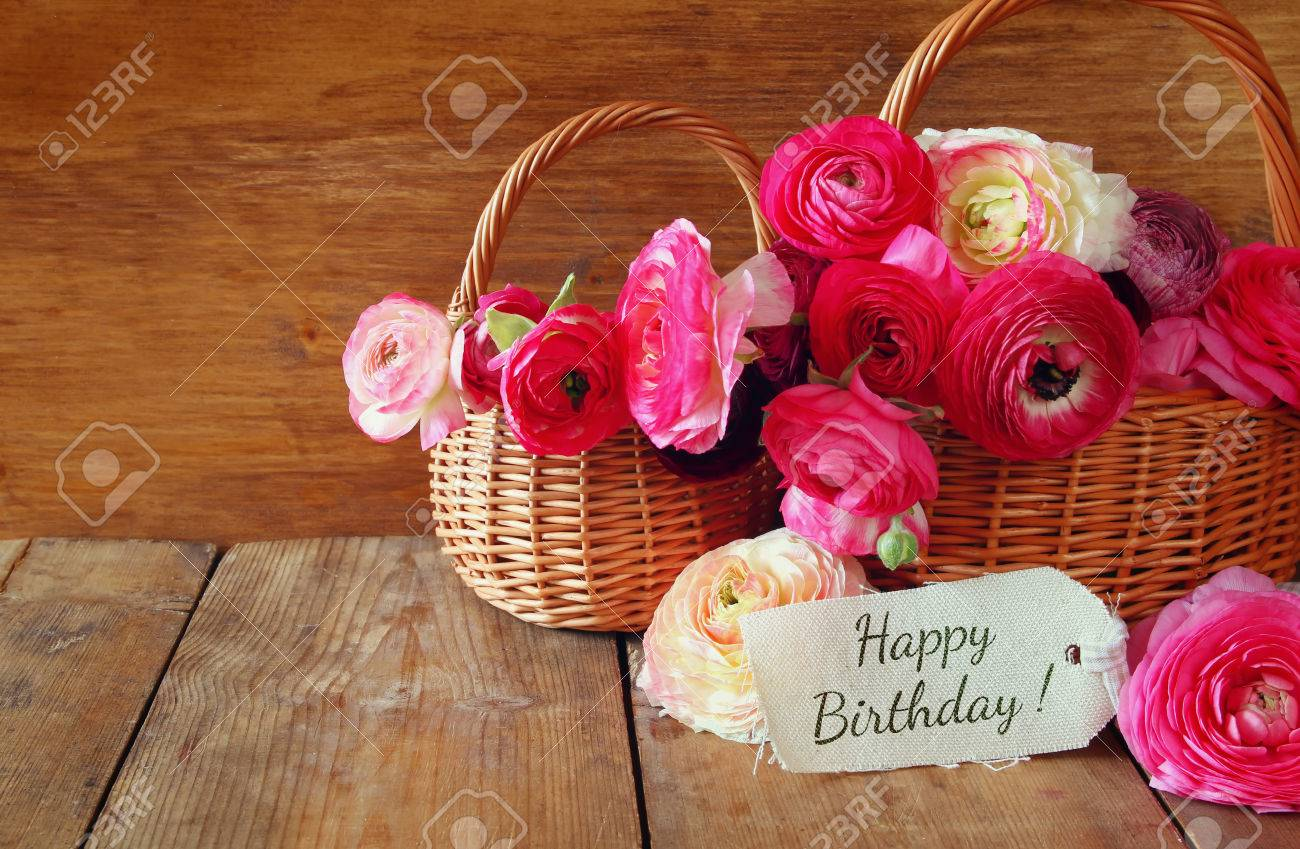 Pink flowers in the basket next to card with phrase happy birthday pink flowers in the basket next to card with phrase happy birthday on wooden mightylinksfo