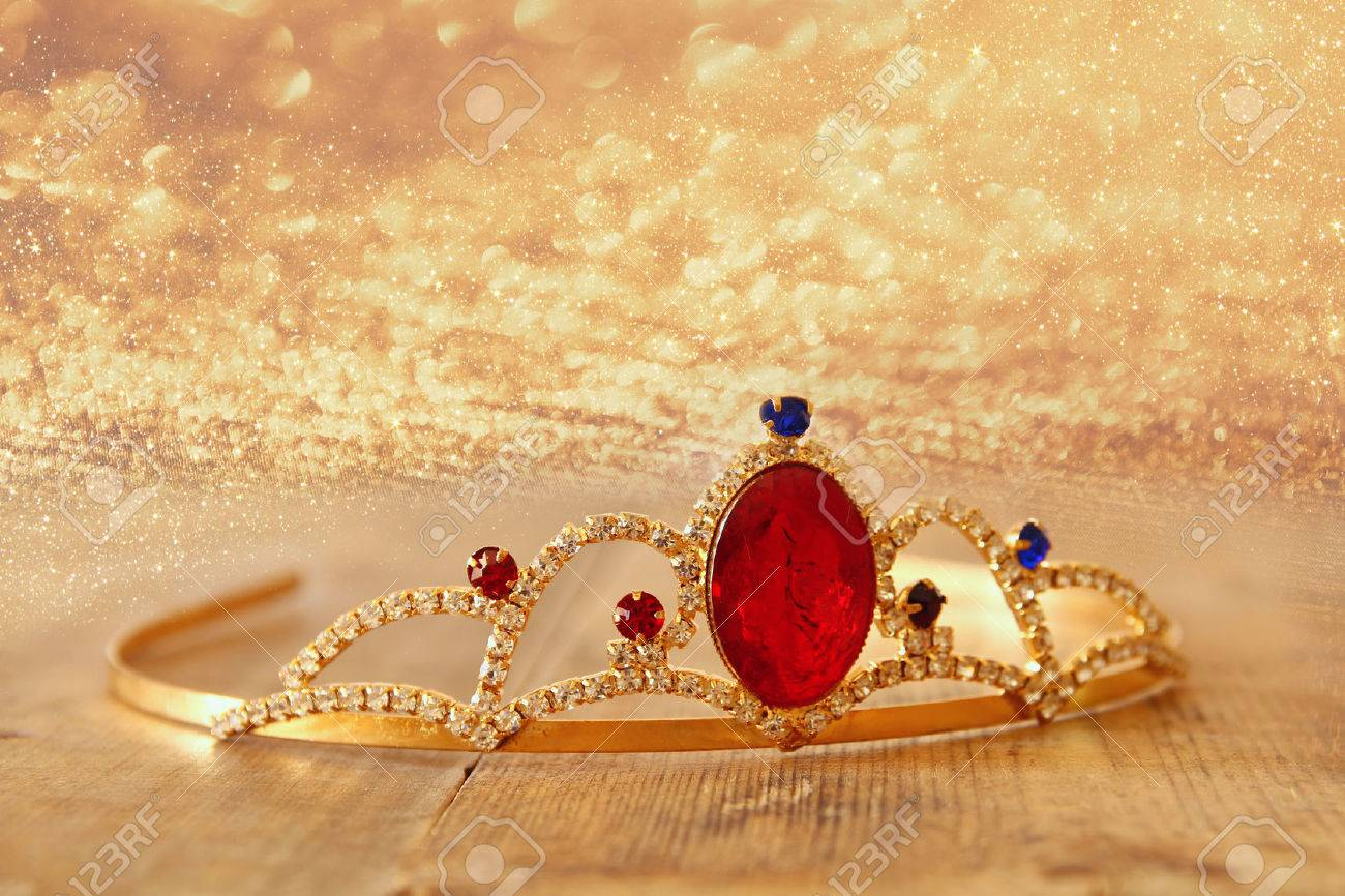 image of gold princes crown on wooden table and glitter background