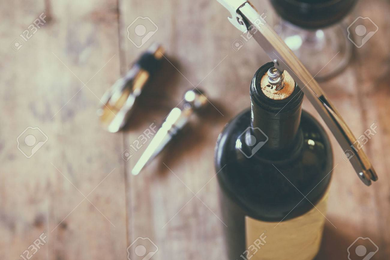 Top View Image Of Red Wine Bottle And Corkscrew Over Wooden Table. Retro  Style Image