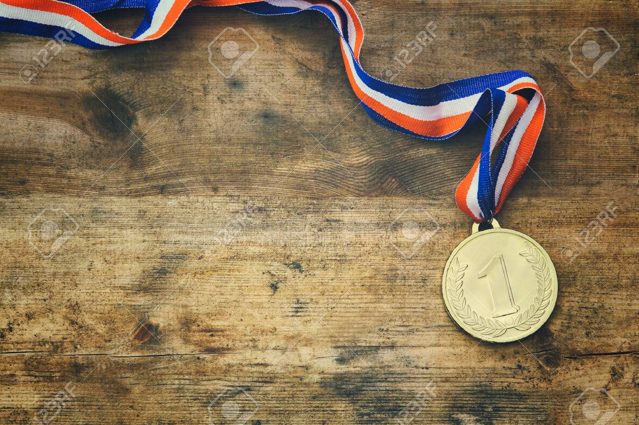 top view image of gold medal over wooden table. - 61203985