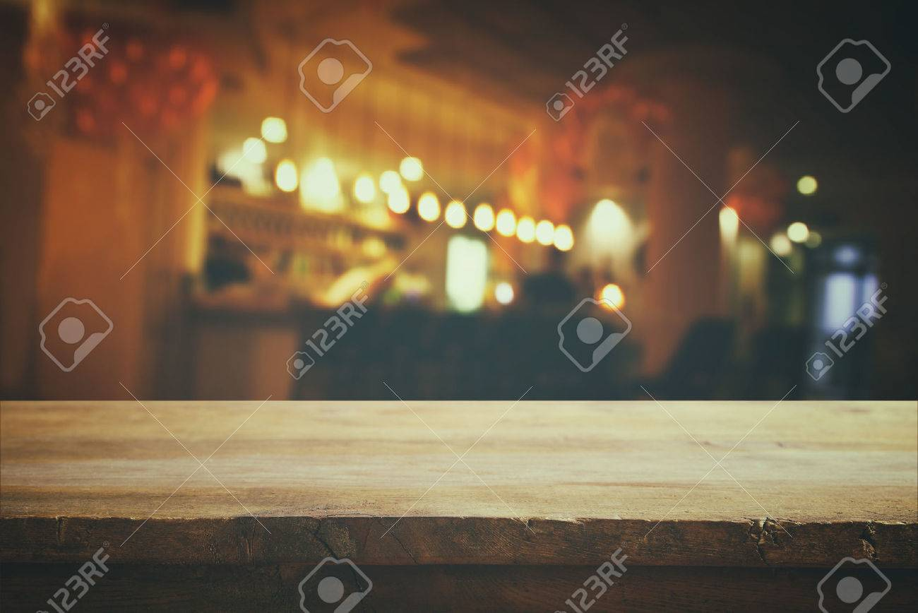 Image of wooden table in front of abstract blurred background of restaurant lights. Retro filtered Stock Photo - 62346118