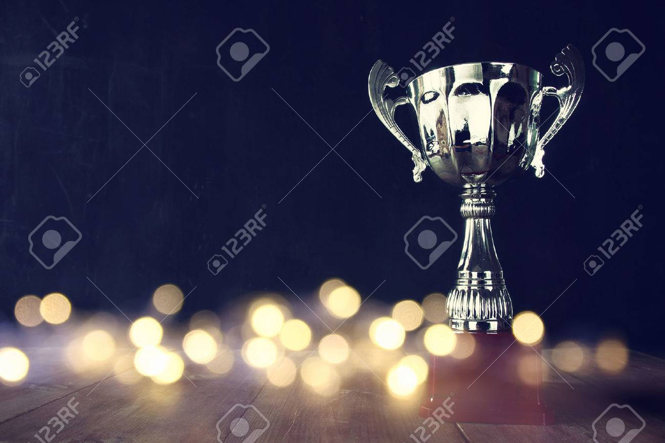 low key image of trophy over wooden table and dark background, with abstract shiny lights Stock Photo - 62414624