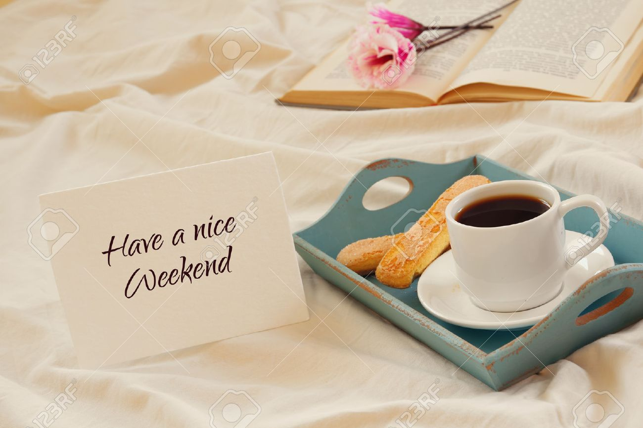 Romantic breakfast in the bed: cookies, hot coffee, flowers and note with the text: HAVE A NICE WEEKEND Stock Photo - 63818461