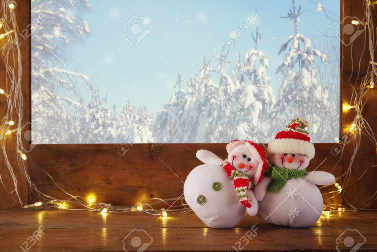 Old Window Sill With Gold Christmas Lights And Cute Snowmen In Front Of Dreamy Winter Snow