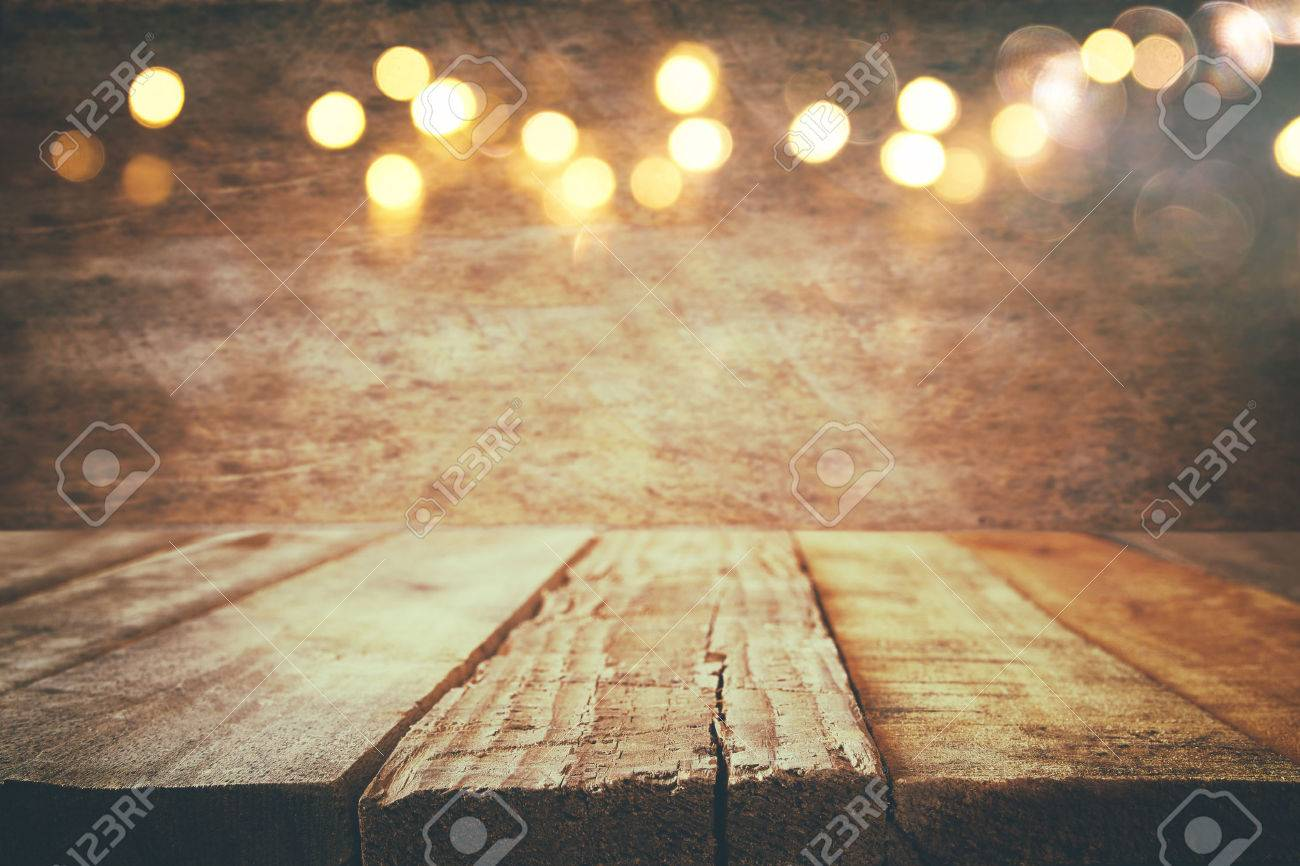 empty table in front of Christmas warm gold garland lights on wooden rustic background. selective focus Stock Photo - 65638931